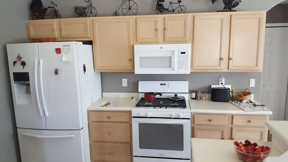 Wide shot of kitchen with wood grain cabinets