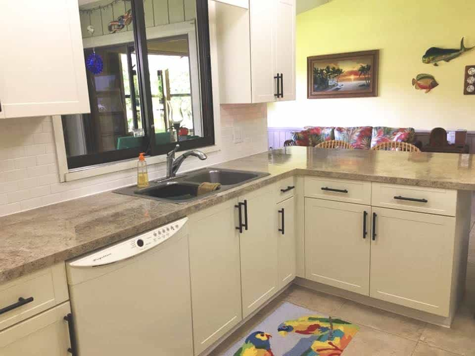 Kitchen with updated white cabinets and tan granite countertop