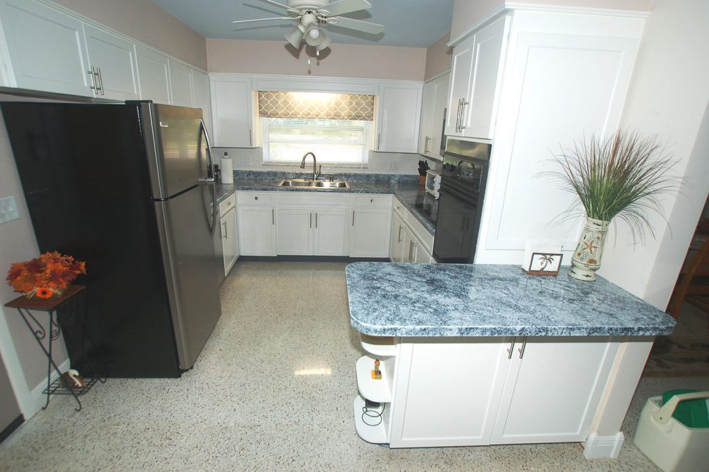 White cabinets with blue granite counters in kitchen