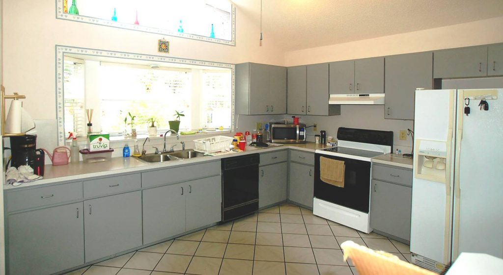 Grey cbainets and white countertops in old kitchen