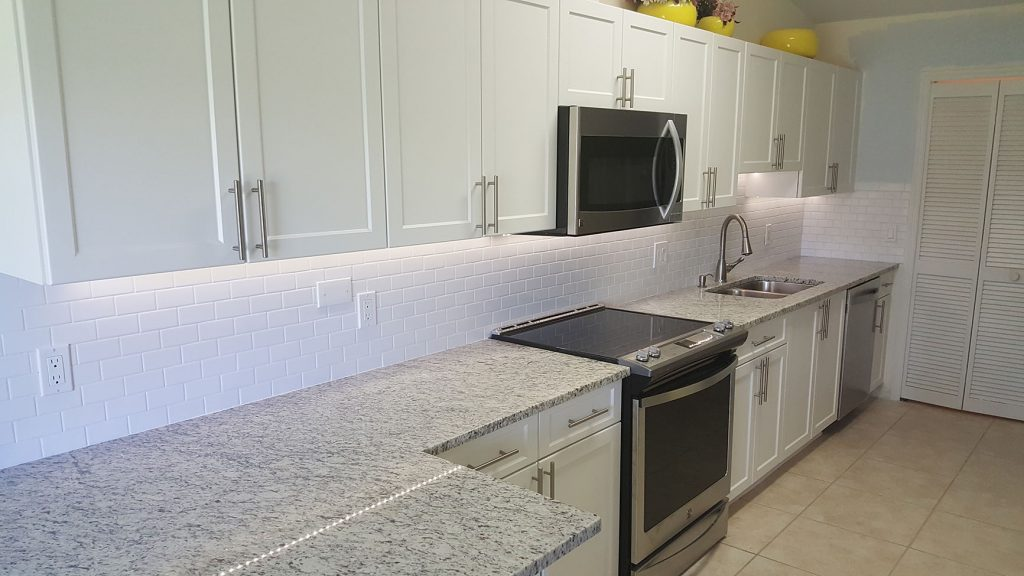 Bright kitchen with new white cabinets and granite counters
