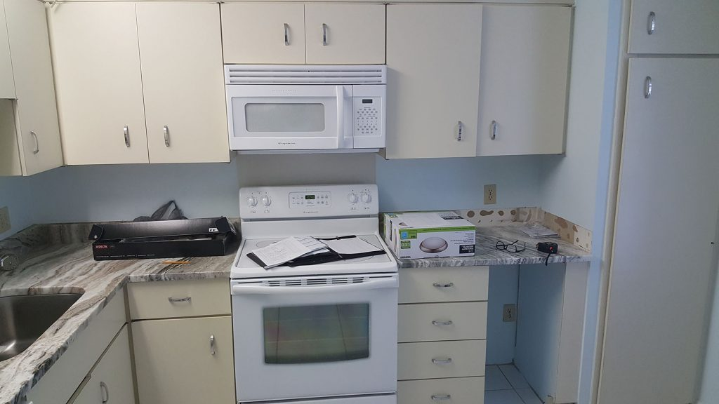 Microwave and stove amongst older cabinets
