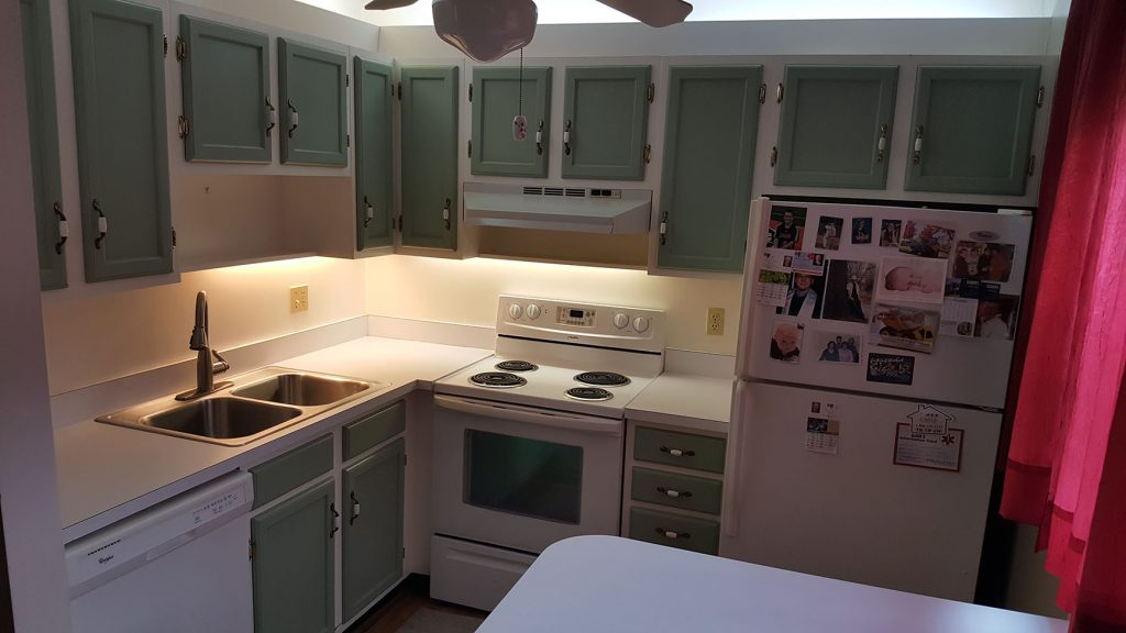 Outdated kitchen with green cabinets
