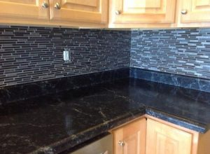 Dark granite countertop and backsplash